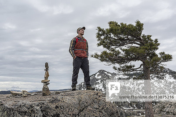 Low angle view of man standing on mountain against cloudy sky in forest
