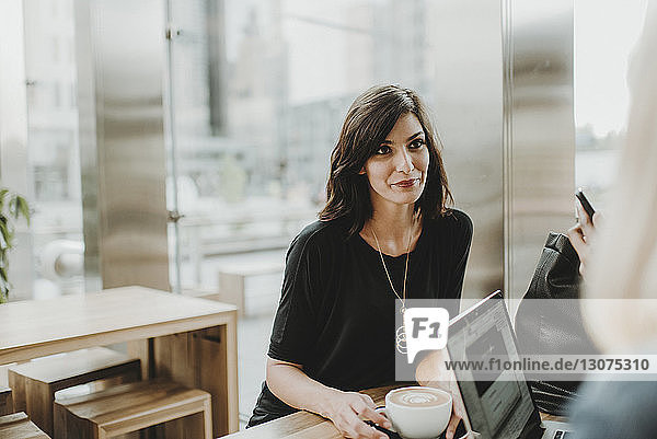 Woman with coffee cup looking away while sitting by laptop computer in cafe