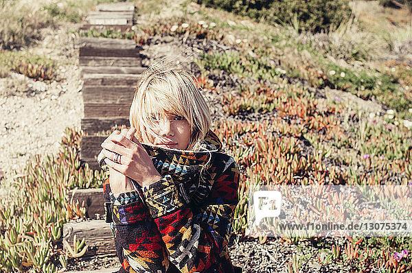 Porträt einer selbstbewussten Frau in Pullover  die auf Holzstufen am Hügel sitzt
