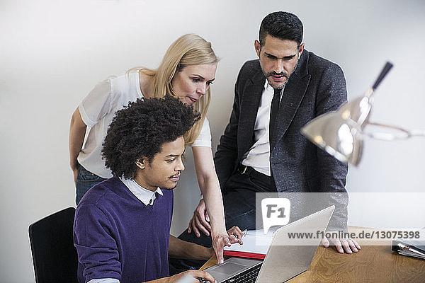 Geschäftskollegen mit Laptop am Schreibtisch im Kreativbüro
