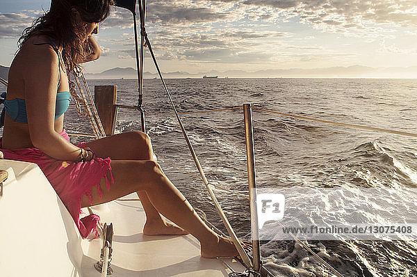 Seitenansicht einer Frau  die bei Sonnenuntergang im Boot auf dem Meer gegen den Himmel sitzt Seitenansicht einer Frau, die bei Sonnenuntergang im Boot auf dem Meer gegen den Himmel sitzt