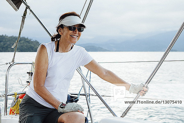 Happy woman sitting in sailboat on sea