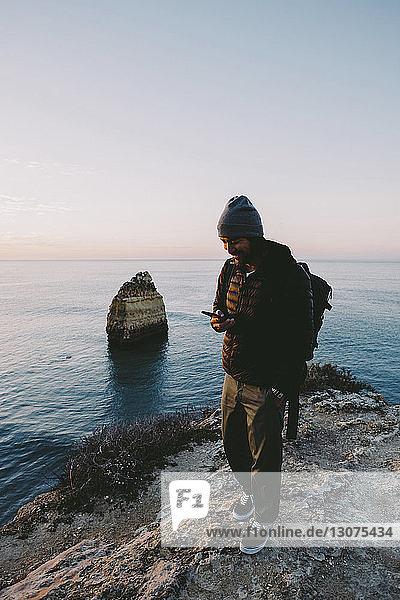 Mann benutzt Smartphone,  während er bei Sonnenuntergang auf einer Felsformation gegen den Himmel steht