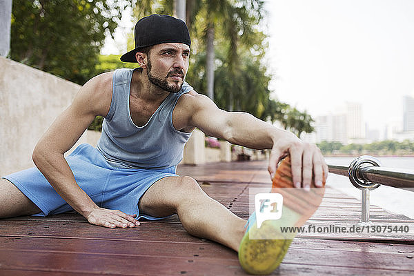 Man sitting and stretching on wooden walkway by river
