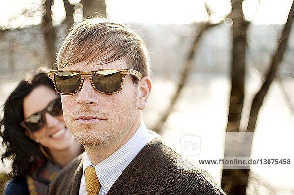 Couple wearing sunglasses against bare trees