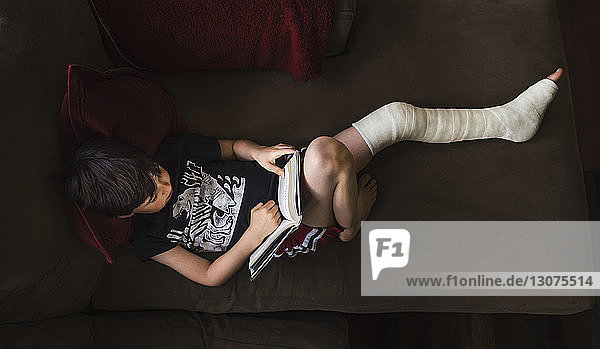 High angle view of boy with broken leg reading book while lying on sofa at home