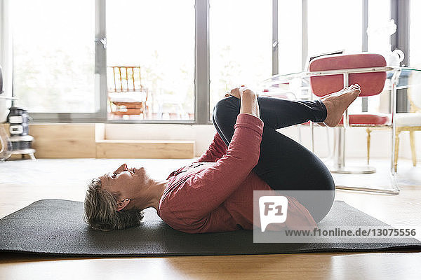 Side view of mature woman exercising at home