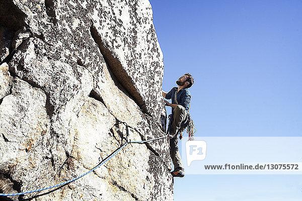 Tiefwinkelansicht eines Mannes beim Klettern gegen klaren Himmel