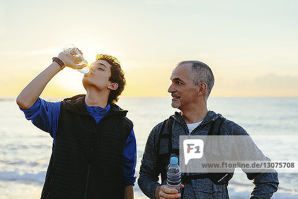 Father looking at son drinking water while standing against sea and sky during sunset