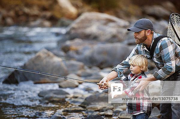 Vater fischt mit dem Sohn am Fluss im Wald