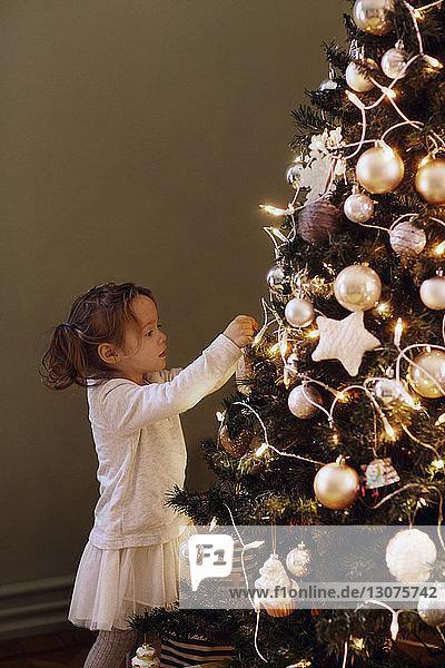 Mädchen schmückt den Weihnachtsbaum zu Hause