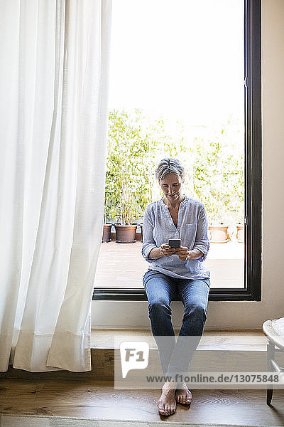 Full length of mature woman using smart phone while sitting on window sill at home