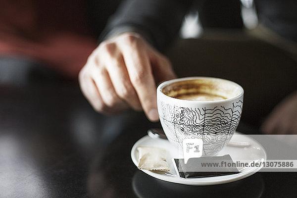 Ausgeschnittenes Bild eines Geschäftsmannes  der in einem Café eine Kaffeetasse am Tisch hält