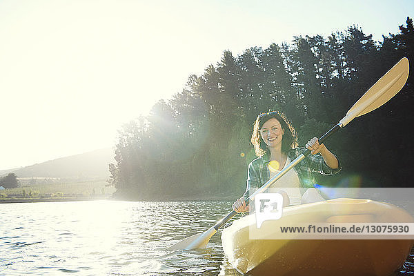 Portrait of happy woman kayaking on lake against sky during sunny day