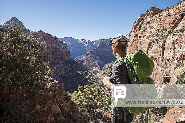 Wanderer mit Rucksack beim Anblick von Felsformationen in der Wüste