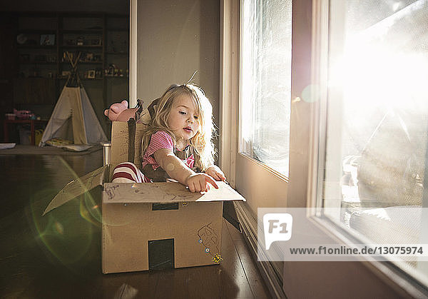 Cute girl sitting in cardboard box by door at home