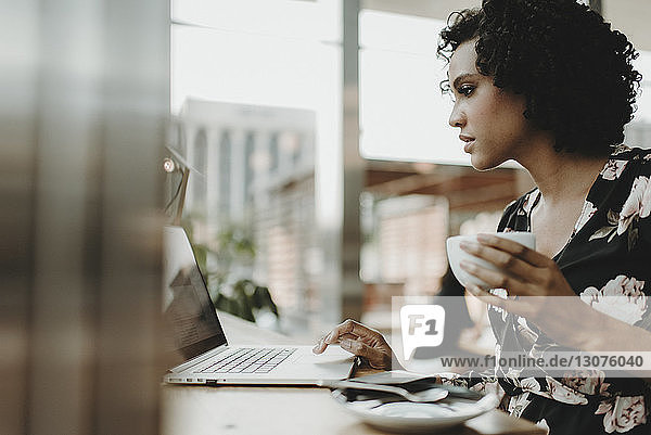 Woman holding coffee cup while using laptop computer on table in cafe