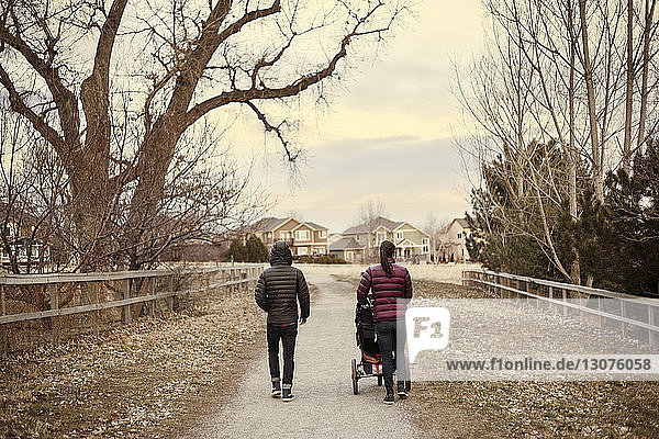 Rückansicht eines Mannes und einer Frau  die im Winter mit Kinderwagen auf der Straße unterwegs sind