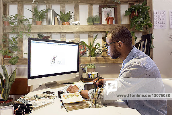 Side view of male illustrator making painting on computer in creative office