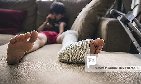 Boy with fractured leg sitting on sofa at home