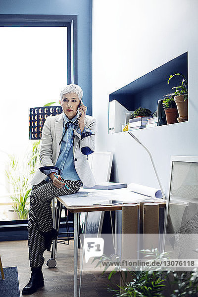 Woman talking on phone while sitting on desk in office