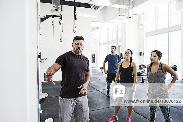 Instructor explaining athletes in crossfit gym