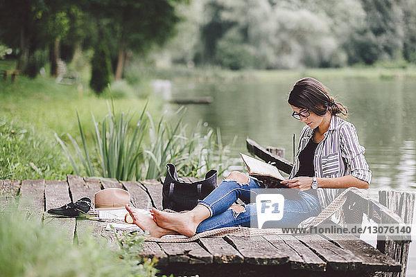 Frau liest Buch  während sie am Pier am See im Wald sitzt