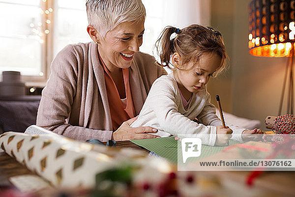 Glückliche Großmutter hilft Enkelin beim Zeichnen zu Hause
