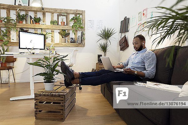 Male illustrator using laptop while sitting on sofa in creative office