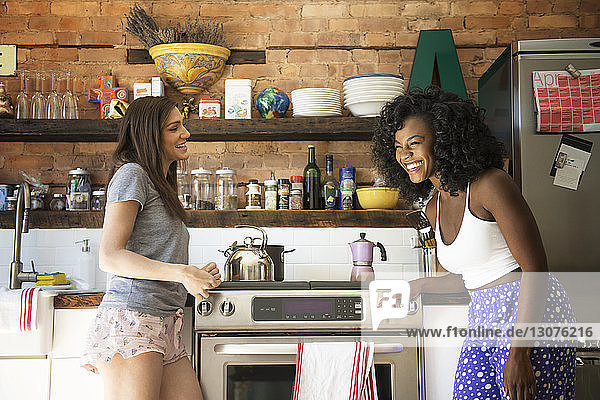 Female friends laughing and enjoying at kitchen
