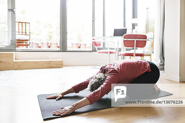 Mature woman practicing yoga in child's pose at home