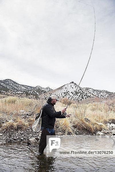 Mann hält Angelrute  während er im Fluss gegen Berge und Himmel steht