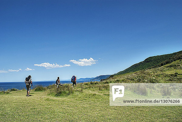 Hikers climbing mountain by sea against blue sky