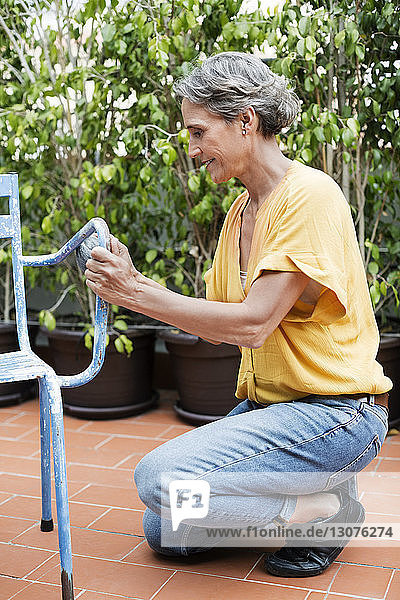 Side view of mature woman scrubbing metallic chair with steel wool at yard