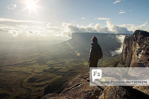 Rückansicht eines Mannes  der an einem sonnigen Tag auf einer Klippe steht