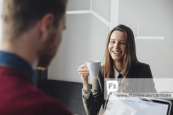 Fröhliche Geschäftsfrau trinkt Kaffee mit Mann im Cafe