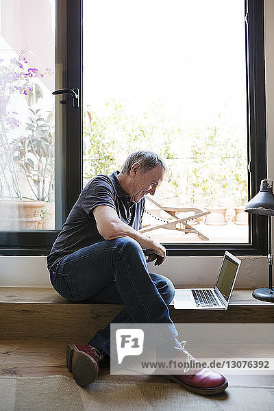 Happy senior man using laptop while sitting by window at home