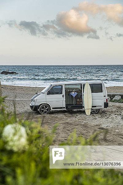 Wohnmobil am Strand gegen den Himmel bei Sonnenuntergang geparkt