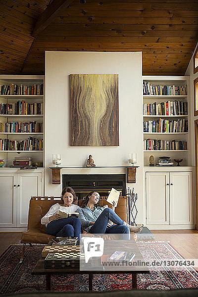 Tochter und Mutter lesen Bücher  während sie auf dem Sofa im Wohnzimmer sitzen