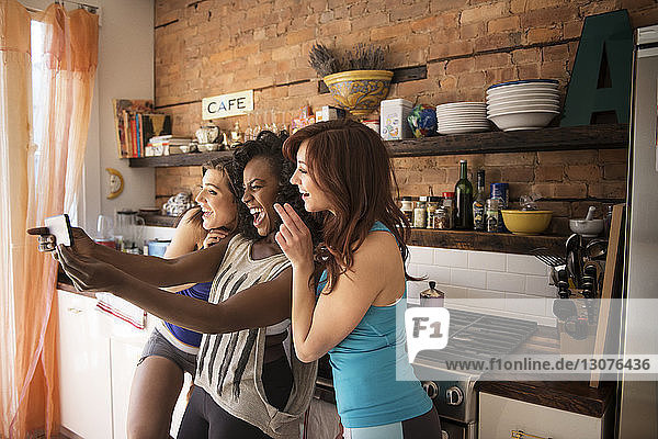 Happy friends taking selfie while standing at kitchen counter at home