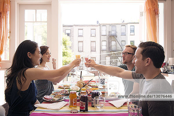 Friends toasting drink while having meal at home