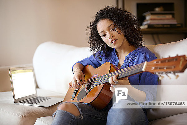Woman practicing guitar while sitting on sofa at home