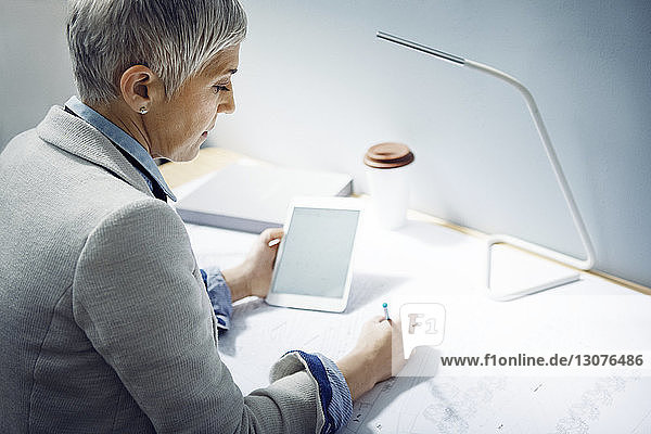 Woman using tablet while writing on paper at table in office