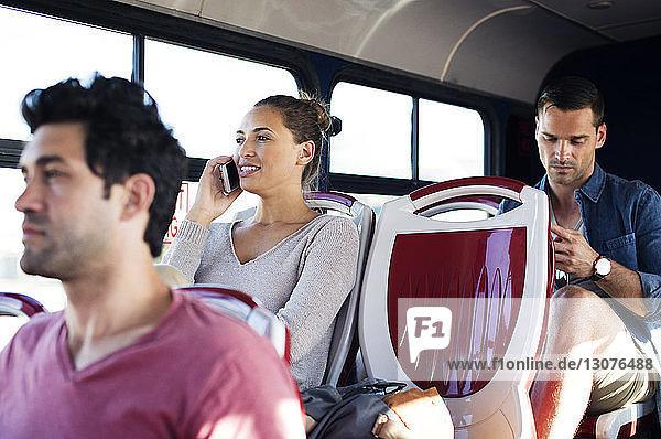 Frau telefoniert mit einem Mobiltelefon  während sie mit anderen Fahrgästen im Reisebus unterwegs ist