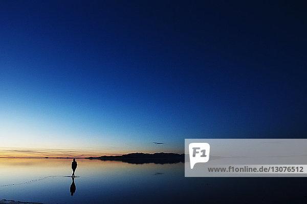 Silhouettenfrau steht bei Sonnenuntergang im Meer