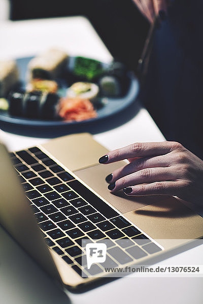 Cropped hand on businesswoman using laptop computer while having food at desk in home office