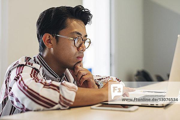 Geschäftsmann mit Laptop-Computer am Konferenztisch im Büro
