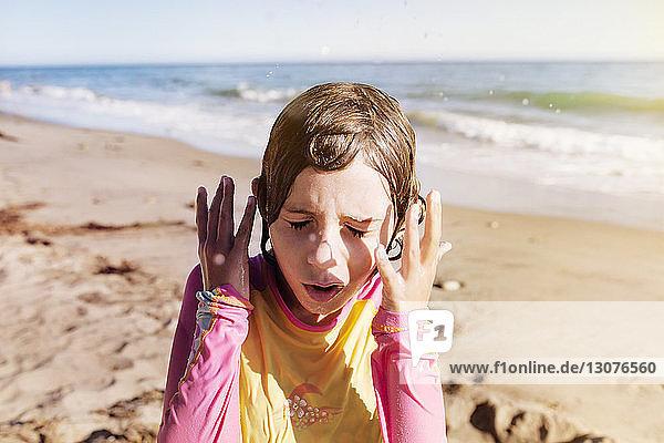 Nahaufnahme eines nassen Mädchens  das an einem sonnigen Tag am Strand steht
