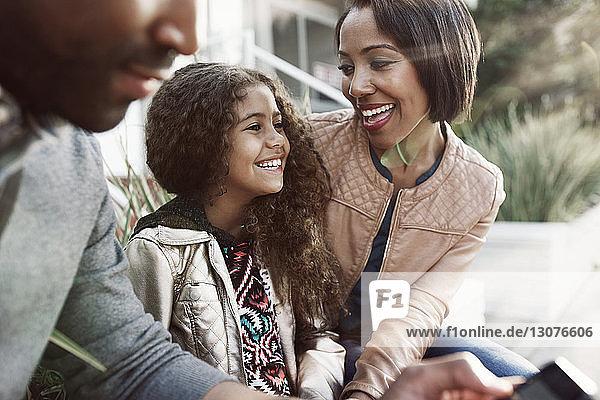 Glückliche Mutter und Tochter sitzen neben einem Mann auf dem Bürgersteig