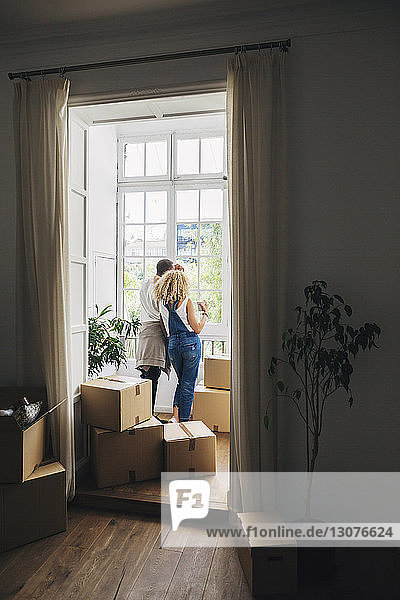 Rear view of couple looking through window while standing in new house seen through doorway
